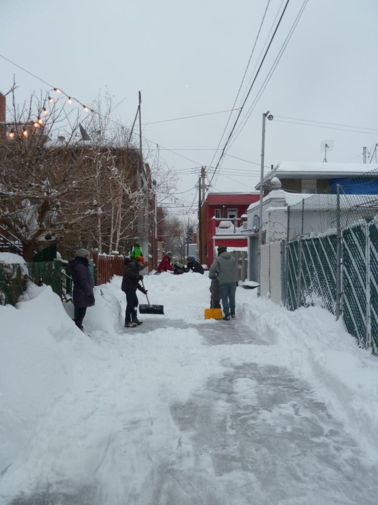 Les voisins en action pour déneiger la patinoire