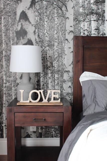 murale de forêt de bouleau noir et blanc et lampe en béton dans une chambre à coucher