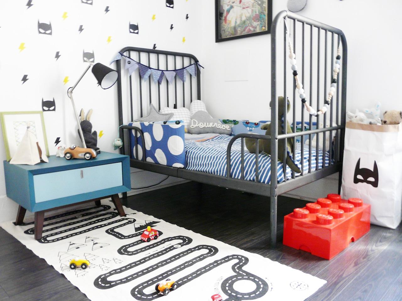 Chambre d'enfant décorée sur le thème Superhéros avec un tapis piste de course de voiture, des stickers muraux et un mot en tricotin