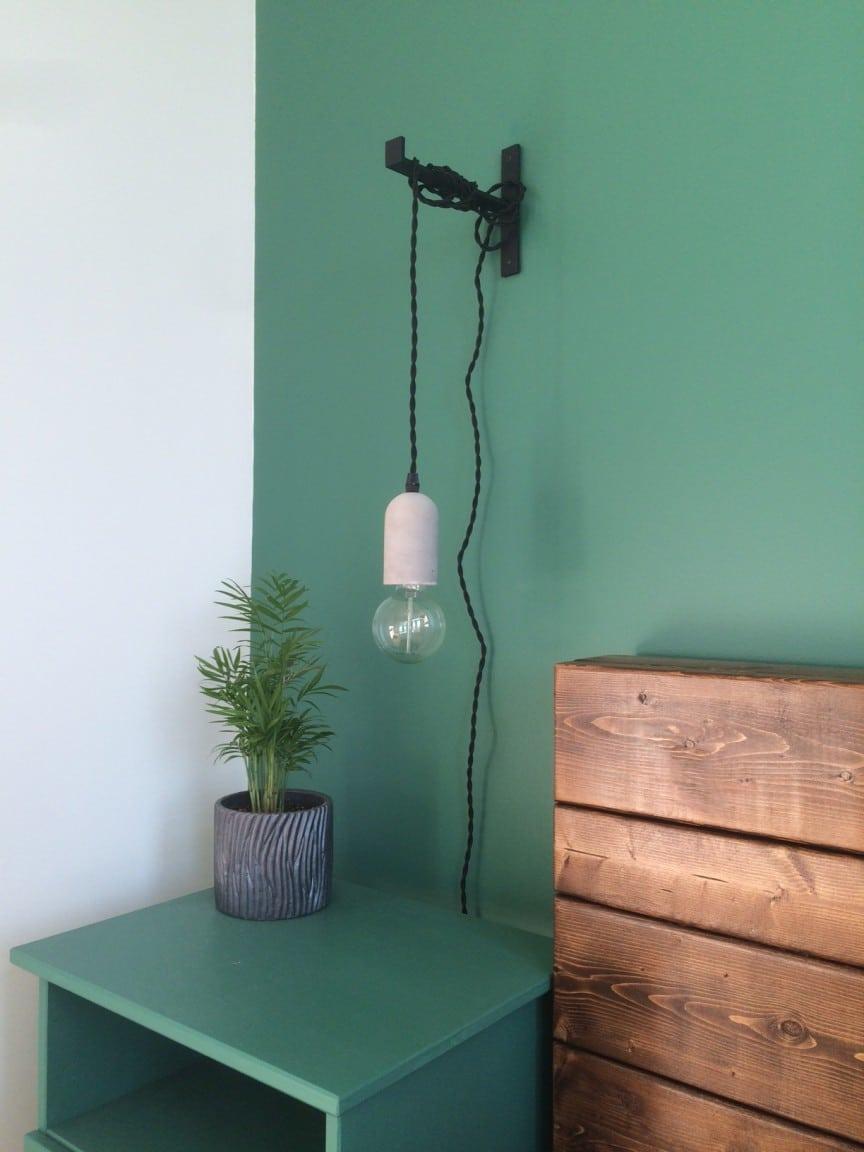 chambre verte avec équerre et luminaire suspendu à une équerre en fonte