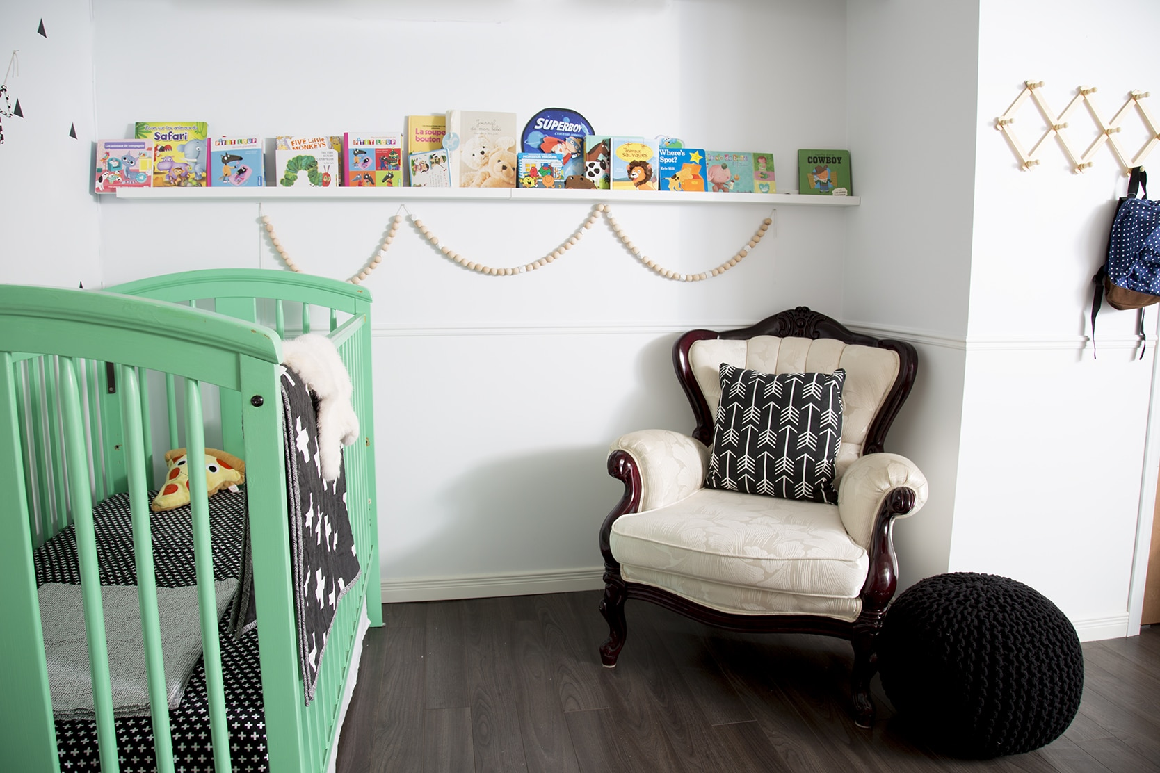 chambre de bébé garçon de style scandinave avec un berceau peint en vert et des touches de noir et blanc / Boy's nursery in a scandinavian style with a green crib and white, black and wood decoration pieces.