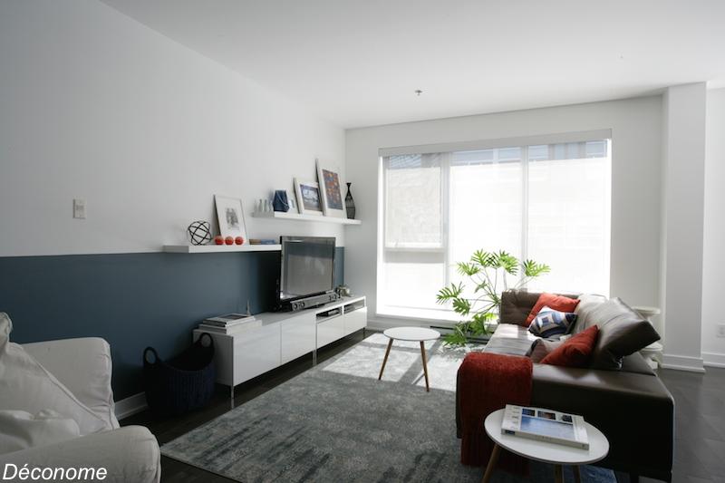 relooking salon avec un demi mur peint en bleu et des étagères flottantes qui intègrent la télé