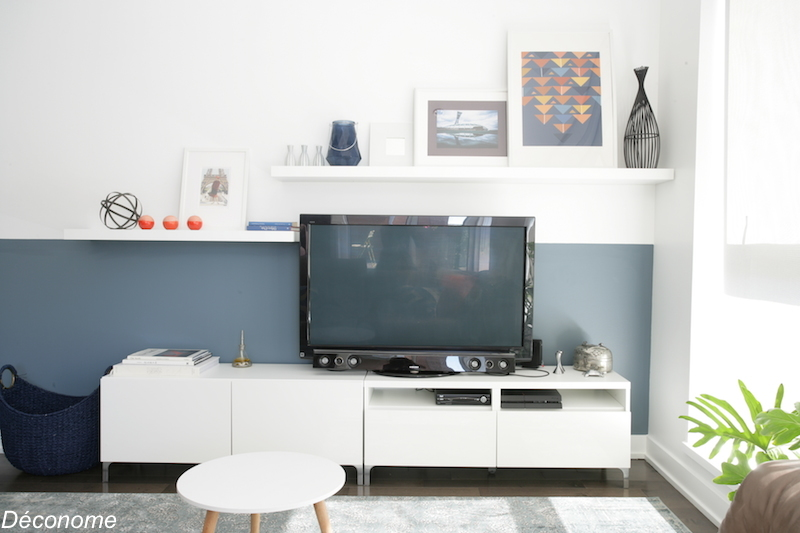 étagère avec cadres superposés sur un demi-mur peint en bleu