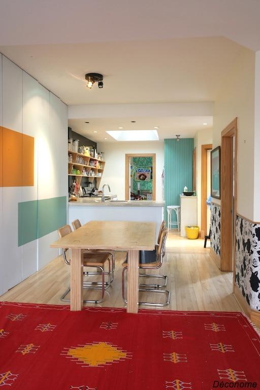 tapis marocain et intérieur bohème et coloré. Table fabriquée en contreplaqué. Murs recouverts de tissus