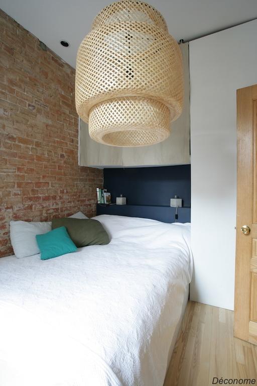 chambre avec mur de brique et mur bleu ambiance naturelle. Luminaire en rotin / ratan lampshade natural bedroom with a brickwall
