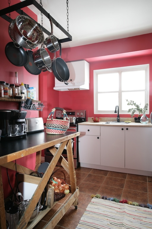 établi en bois et crémaillère à chaudrons / Red kitchen with wooden table and hanging pot rack