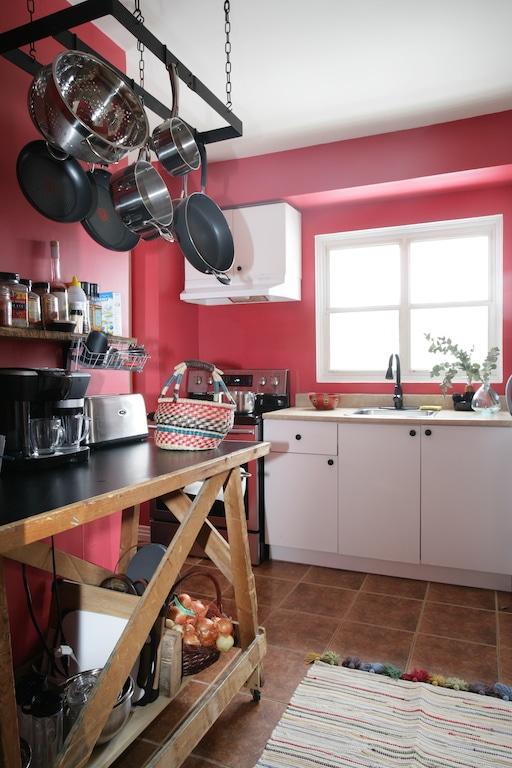 établi en bois et crémaillère à chaudrons / Red kitchen with wooden table and hanging pot rack