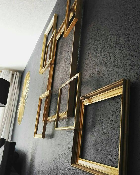 cadres dorés superposés sur un mur noir / golden frames on a black wall