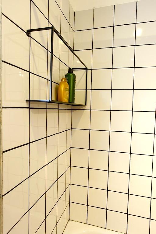 Etagere metal noire dans la douche