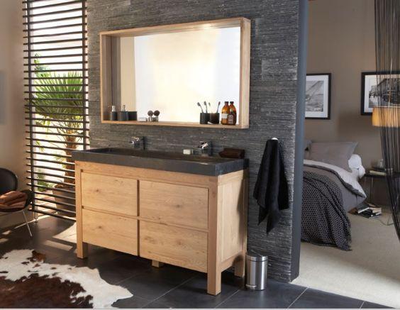 Mur de pierre dans salle de bain ouverte sur la chambre. Tons gris et bois