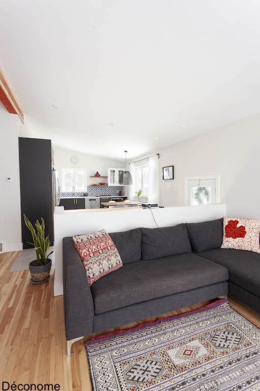 Ouverture d'un salon sur une cuisine avec cage d'escalier au milieu
