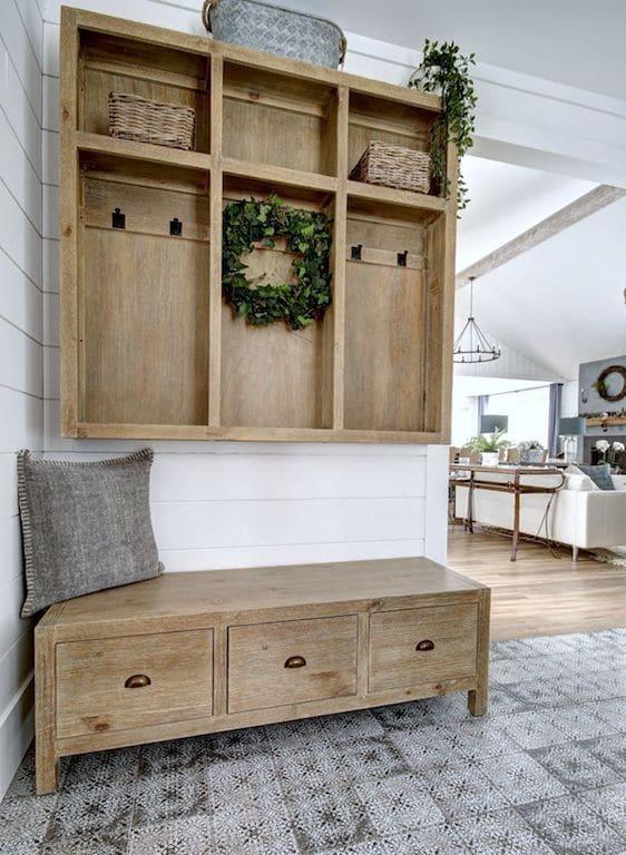 banc d'entrée et casier en bois dans une entrée de style farmhouse. Carreaux style ciment à motifs