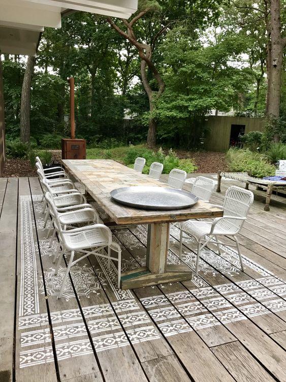 pochoir de mandala géant peint sur terrasse en bois. Faux tapis sous la table