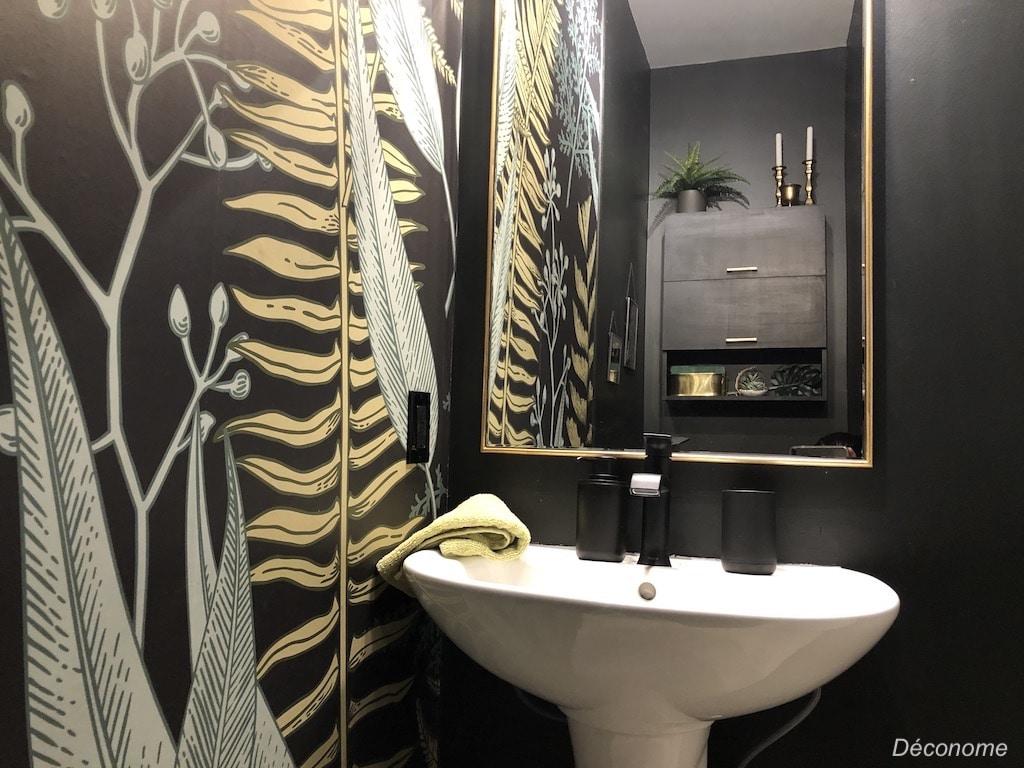 Papier peint noir et fougères dans une salle d'eau noire
