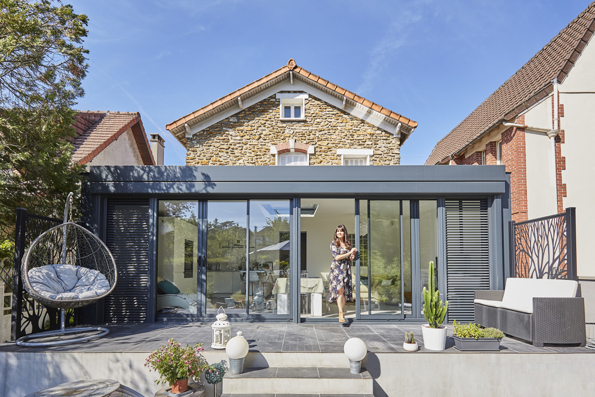 véranda moderne à toit plat devant vieille maison en pierre