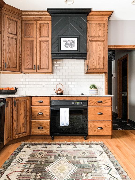 armoires de cuisine en bois de chêne rajeunie. Hotte cheminée noire