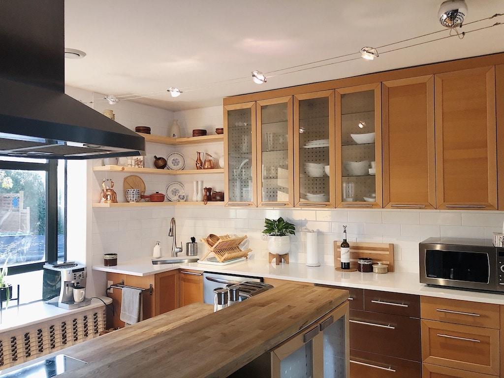 armoires de cuisine en bois modernisées avec comptoir de quartz et carreaux blancs