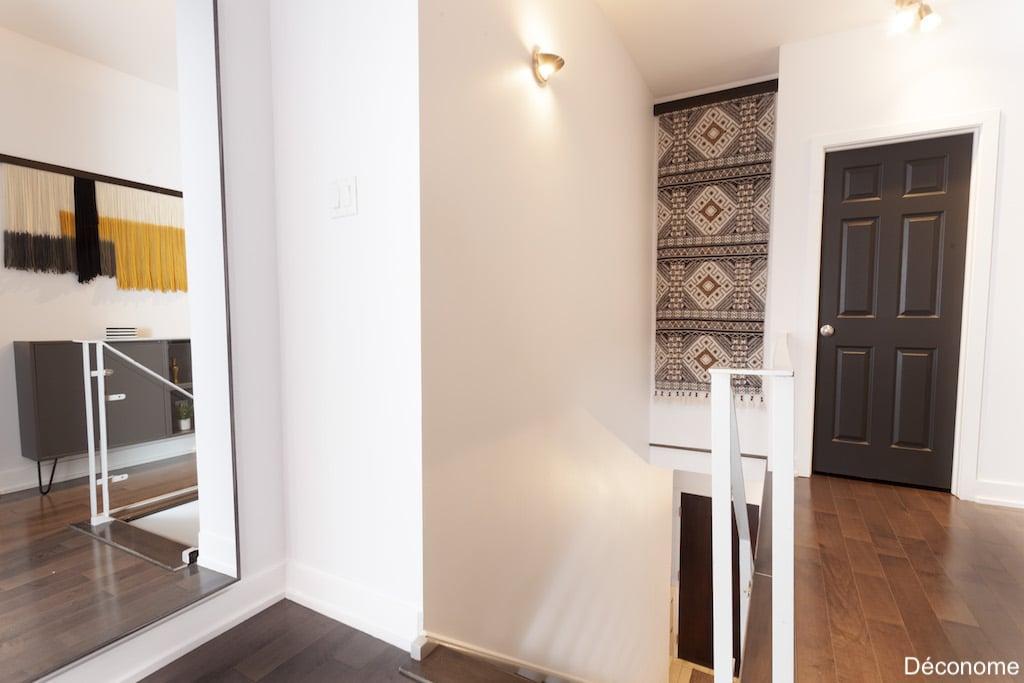 Décoration de couloir avec tapis suspendu dans la cage d'escalier et miroir agrandissant