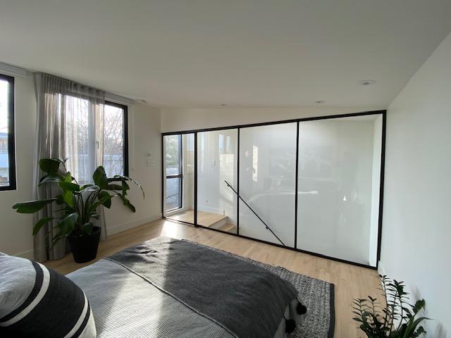mur séparateur vitré entre une cage d'escalier et une chambre